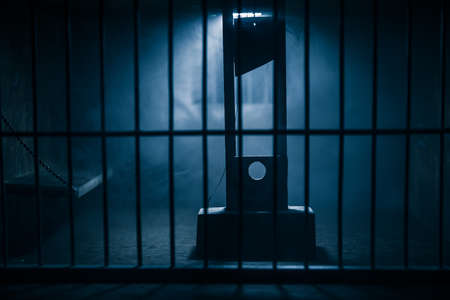 Execution concept. Death penalty guillotine miniature inside old prison. Old prison bars cell lock. Creative artwork decoration. Horror view of Guillotine scale model in the dark