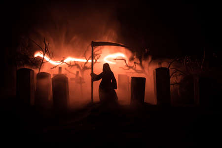 Scary view of grim reaper at cemetery with spooky cloudy sky and fog, Horror Halloween concept. Selective focus 写真素材