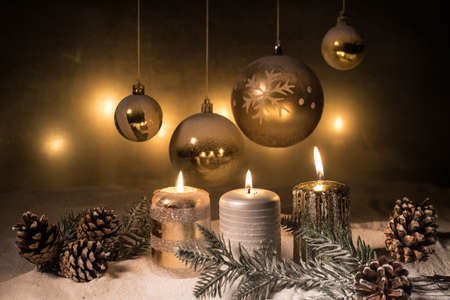 Christmas decoration with burning candles on a dark background. Christmas ornaments over dark golden background with lights. Creative artwork decoration. Archivio Fotografico - 158165512