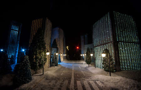 Little miniature city with road and lights. Decorative cute small houses in snow at night in winter. Creative Holiday concept. Christmas and New Year attributes decorated composition. Archivio Fotografico - 158165513