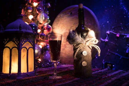 Glass of wine with Christmas decoration. Red wine in crystal glass with bottle on colorful carpet with creative New Year artwork decorations. Copy space Archivio Fotografico - 158165516