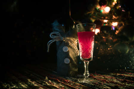 Glass of wine with Christmas decoration. Red wine in crystal glass with bottle on colorful carpet with creative New Year artwork decorations. Copy space Archivio Fotografico - 158165519
