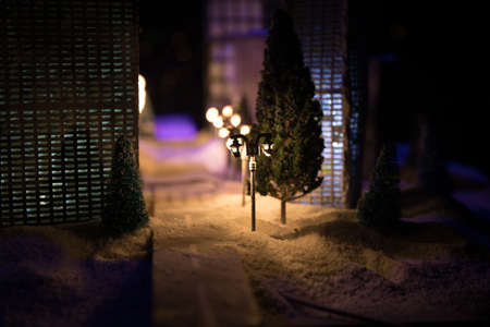 Little miniature city with road and lights. Decorative cute small houses in snow at night in winter. Creative Holiday concept. Christmas and New Year attributes decorated composition. Archivio Fotografico - 158165525