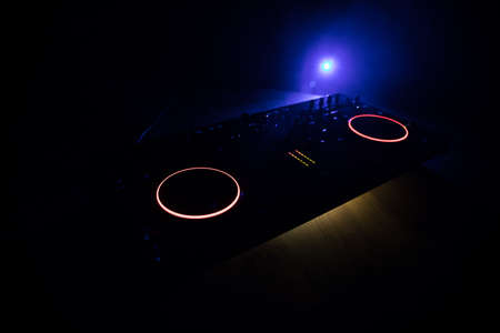 Club music concept. DJ console deejay-mixing desk in dark with colorful light. Mixer equipment entertainment DJ station. Selective focus Archivio Fotografico - 158165527
