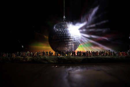 Clublife creative concept. Crowd miniature standing at big disco mirror ball with lights. Night club background. Party lights disco ball and clubbers. Selective focus