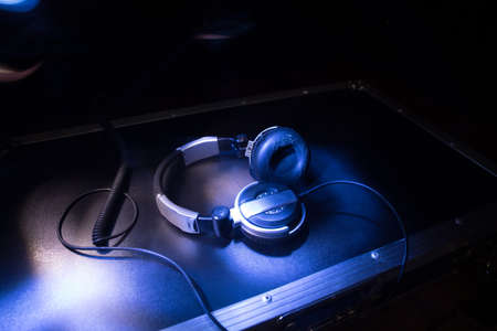 Dj music club concept. Close up headphones on dark background with colorful light. Selective focus Archivio Fotografico