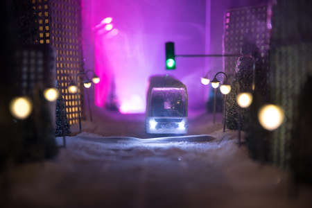 Little miniature city with road and lights. Decorative cute small houses in snow at night in winter. Creative Holiday concept. Christmas and New Year attributes decorated composition. Archivio Fotografico - 158165564