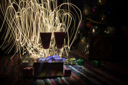 Glass of wine with Christmas decoration. Red wine in crystal glass with bottle on colorful carpet with creative New Year artwork decorations. Copy space Archivio Fotografico - 158165567