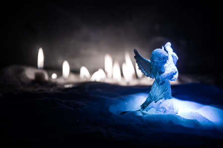 Christmas angel standing on snow with many candles on background. Little white guardian angel in snow. Festive background. Christmas and New Year concept. Selective focus Archivio Fotografico - 158165577