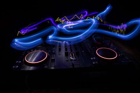 Club music concept. DJ console deejay-mixing desk in dark with colorful light. Mixer equipment entertainment DJ station. Selective focus