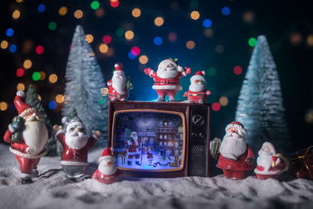Creative Christmas concept. Vintage television set on snow with Santa Claus. Artwork decoration. 免版税图像