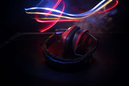Dj music club concept. Close up old vintage headphones on dark background with colorful light. Selective focus 免版税图像