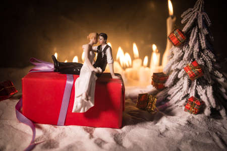 Winter holidays and love concept. Couple doll figures and Christmas decorations on snow with many candles on background. Empty space for your text 免版税图像