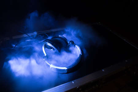 Dj music club concept. Close up headphones on dark background with colorful light. Selective focus 免版税图像