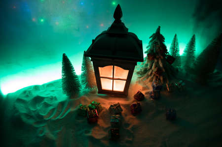Christmas lantern on snow with fir tree and moon. Festive dark background. New Year's still-life postcard lamp covered in snow with glowing candle at night. Holiday concept. Artwork 免版税图像