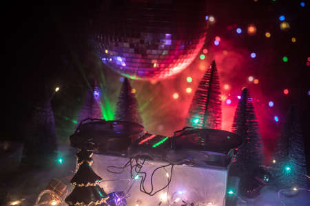 Christmas and New Year club concept. Dj mixer with headphones on snow. Santa Claus is mixing on turntable. Creative miniature artwork decoration on snow. 免版税图像