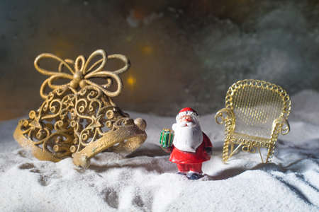 Christmas decorations. Golden Jingle bell miniature standing with beautiful holiday decorated background and traditional holiday attributes. Selective focus. Empty space for your text