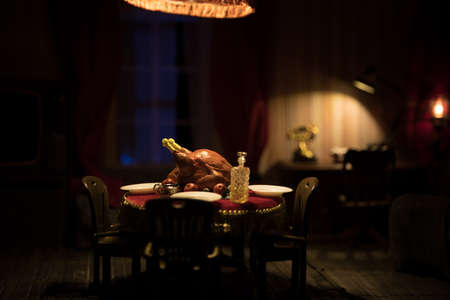 Thanksgiving holiday creative concept. A realistic dollhouse living room with furniture and window at night. Thanksgiving Turkey miniature on table. Selective focus