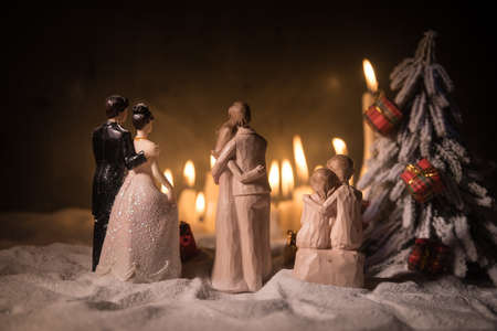 Winter holidays and love concept. Couple doll figures and Christmas decorations on snow with many candles on background. Empty space for your text Imagens