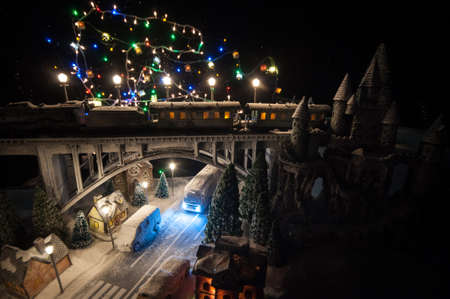 Miniature of winter snowy scene with train on bridge, medieval castle and small city. Holiday attributes. Night scene. New Year and Christmas concept. Creative artwork mini on table decoration