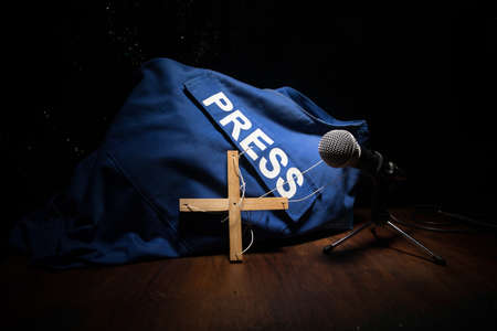 Media Journalism fake news concept. Blue journalist (press) vest in dark with backlight and fog. Puppeteer controls media. Selective focus