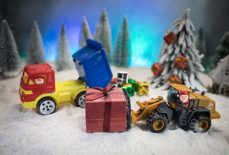 Miniature Gift Box by Forklift Machine on snow, Determined Image for Christmas Holiday and Happy New Year Gift Celebration concept. Empty space for text