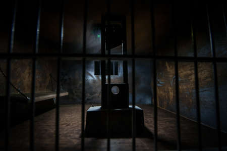 Execution concept. Death penalty guillotine miniature inside old prison. Old prison bars cell lock. Creative artwork decoration. Horror view of Guillotine scale model in the dark Archivio Fotografico