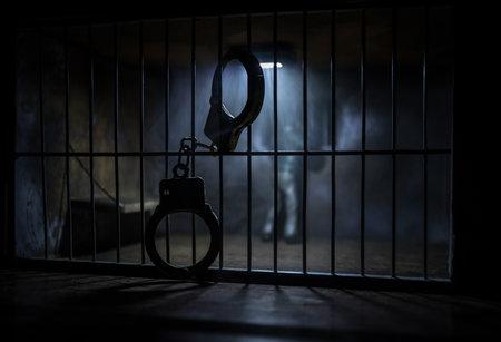 Man in prison man behind bars concept. Old dirty grunge prison miniature. Dark prison interior creative decoration with handcuffs. Selective focus