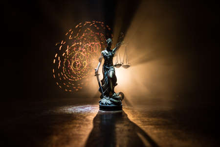 Law concept. Miniature colorful artwork decoration with fog and backlight. The Statue of Justice - lady justice or Iustitia / Justitia the Roman goddess of Justice. Selective focus