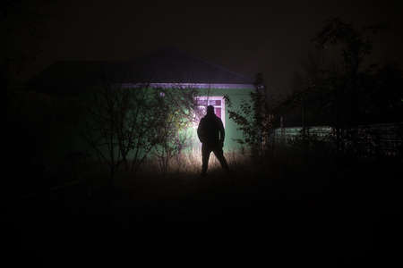 Old house with a Ghost in the forest at night. Horror silhouette at the window. Horror Halloween concept Alone man silhouette standing near window of house at night. Selective focus