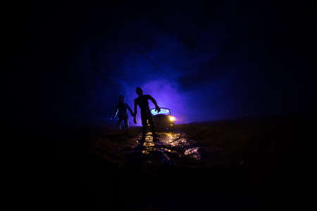 photo of a car stopped on the road lighting up a zombies. Silhouette terrible zombie night near the car. Miniature decoration. Selective focus Archivio Fotografico