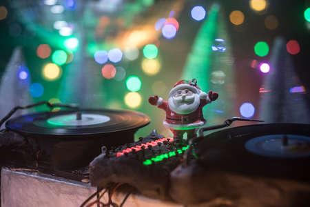 Christmas and New Year club concept. Dj mixer with headphones on snow. Santa Claus is mixing on turntable. Creative miniature artwork decoration on snow. Archivio Fotografico
