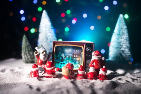 Creative Christmas concept. Vintage television set on snow with Santa Claus. Artwork decoration. Archivio Fotografico