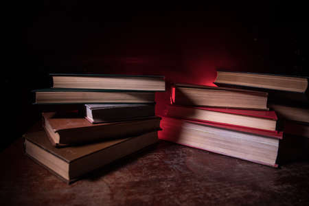 A stack of old books. Vintage book on wooden table. Magic lightning around a glowing book in the room of darkness. Selective focus
