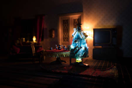Christmas and New Year holidays concept. A realistic dollhouse living room with furniture and window at night. Artwork table decoration with handmade realistic dollhouse. Selective focus.