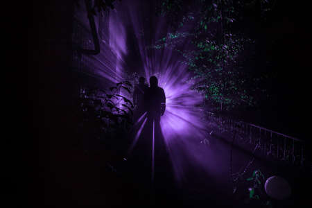 Silhouette of person standing in the dark forest with light. Horror halloween concept. strange silhouette in a dark spooky forest at night
