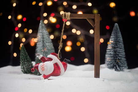 Funny New Year concept. Santa claus figurine is hanged upside down on scaffold. Creative artwork decoration with Christmas attributes on snow.
