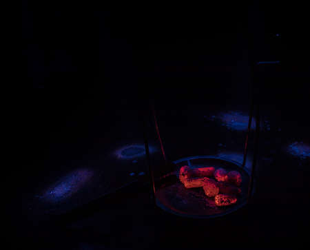 Close-up of burning charcoal cubes. Action. Cubes of embers burning in bowl for smoking hookah. Creative artwork decoration on dark background. Empty space. Selective focus Archivio Fotografico