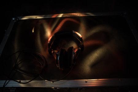 Dj music club concept. Close up headphones on dark background with colorful light. Selective focus Archivio Fotografico