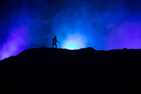 War Concept. Military silhouettes fighting scene on war fog sky background, World War Soldiers Silhouette Below Cloudy Skyline At night. Selective focus Archivio Fotografico