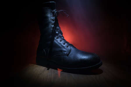 War concept. Old military shoe in a dark toned foggy background. Creative concept of military aggression. Selective focus
