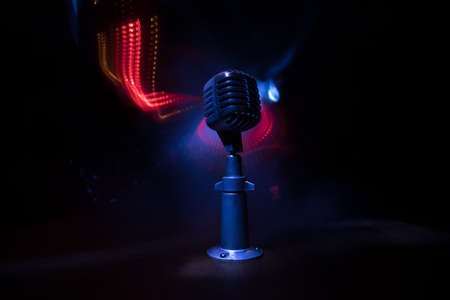 Retro style microphone on background with backlight. Vintage silver Microphone for sound, music, karaoke. Speech broadcast equipment. Live pop, rock musical performance. Selective focus Archivio Fotografico