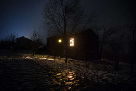 Wooden house in winter forest. Mountain house in the snow at night. Misty night. Long exposure shot Archivio Fotografico