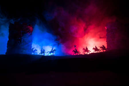 Medieval battle scene. Silhouettes of figures as separate objects, fight between warriors at night. Creative artwork decoration. Foggy background. Selective focus