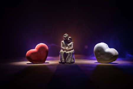 Valentines background. Valentine's Day heart on a dark wooden table. Little love couple figure close up. Heart in fire. Dark toned foggy background. Selective focus Foto de archivo