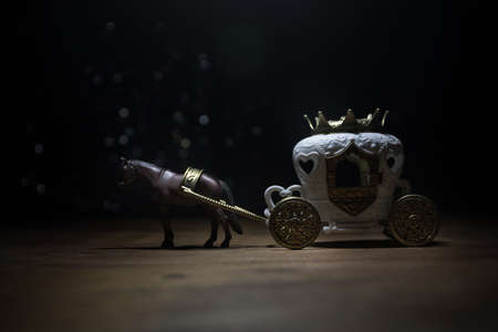 Little carriage with horse miniature on table. Creative decoration on dark toned foggy background. Selective focus Foto de archivo