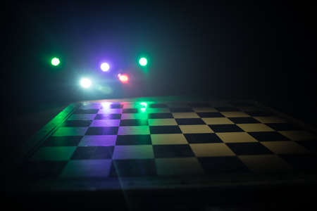 empty chess board with smoke float up on dark background with colorful backlight. Selective focus