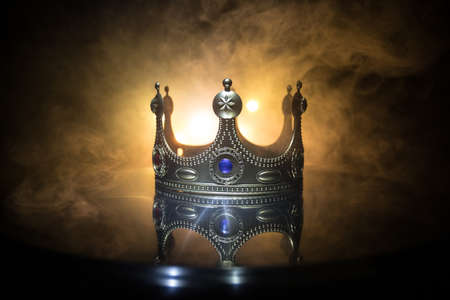 low key image of beautiful queen / king crown over metallic surface. vintage filtered. fantasy medieval period. Selective focus. Colorful backlight