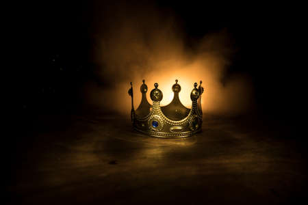 low key image of beautiful queen / king crown over wooden table. vintage filtered. fantasy medieval period. Selective focus. Colorful backlight Foto de archivo