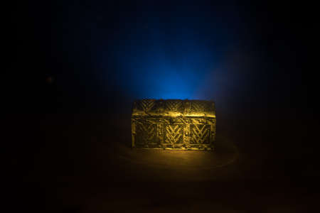 A dark wooden treasure chest with lid closed on wooden table. Selective focus Foto de archivo